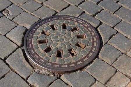 Tombino sul marciapiedi: risarcisce il Comune se la pulizia spetta a terzi