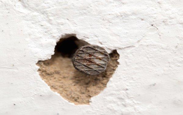 Buchi di chiodi: chi ripara le pareti della casa in affitto?